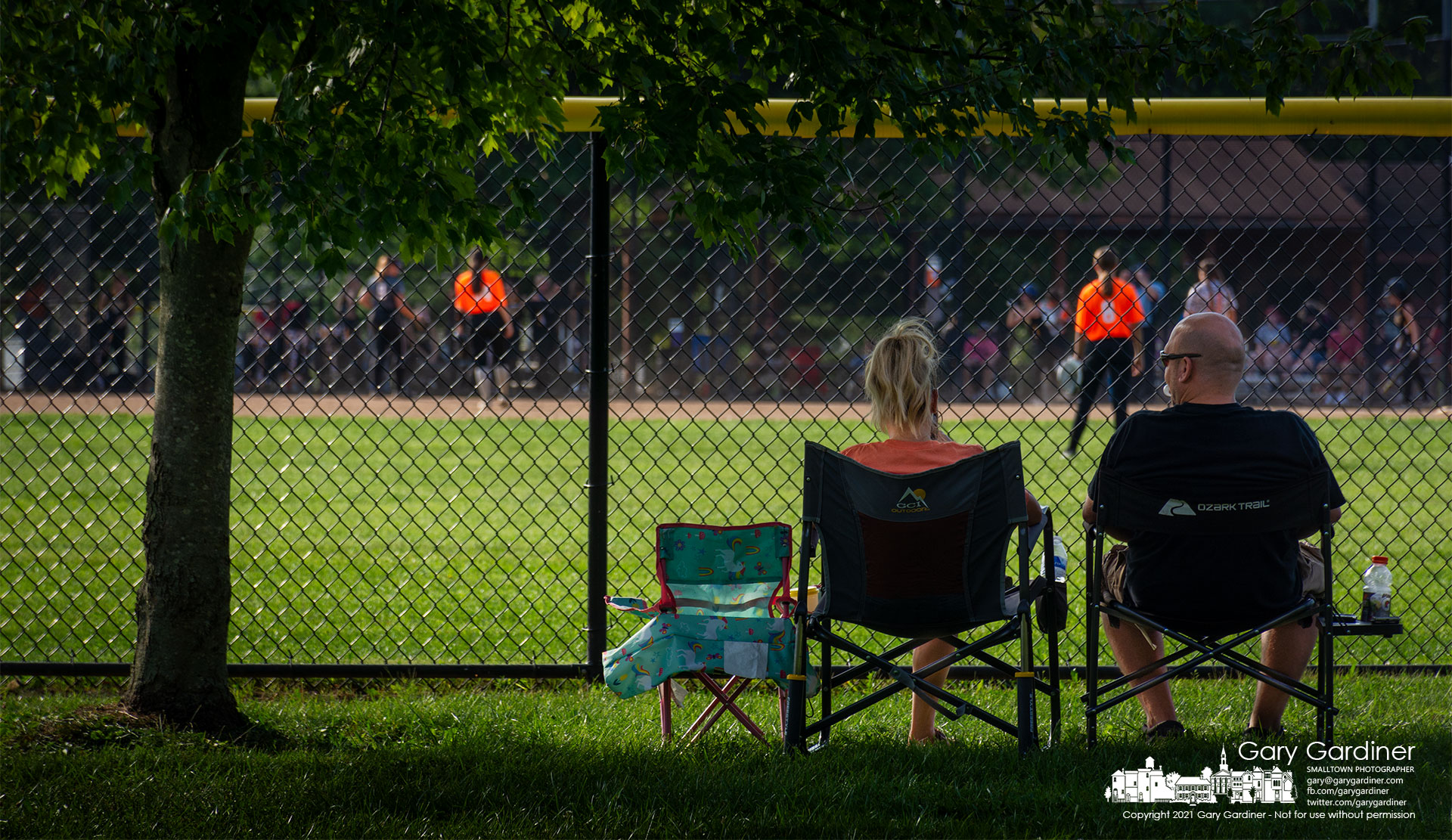 A set of parents watch a softball game at Highlands from reserved seats in the shadow of a maple tree at center field. My Final Photo for Sept. 19, 2021.