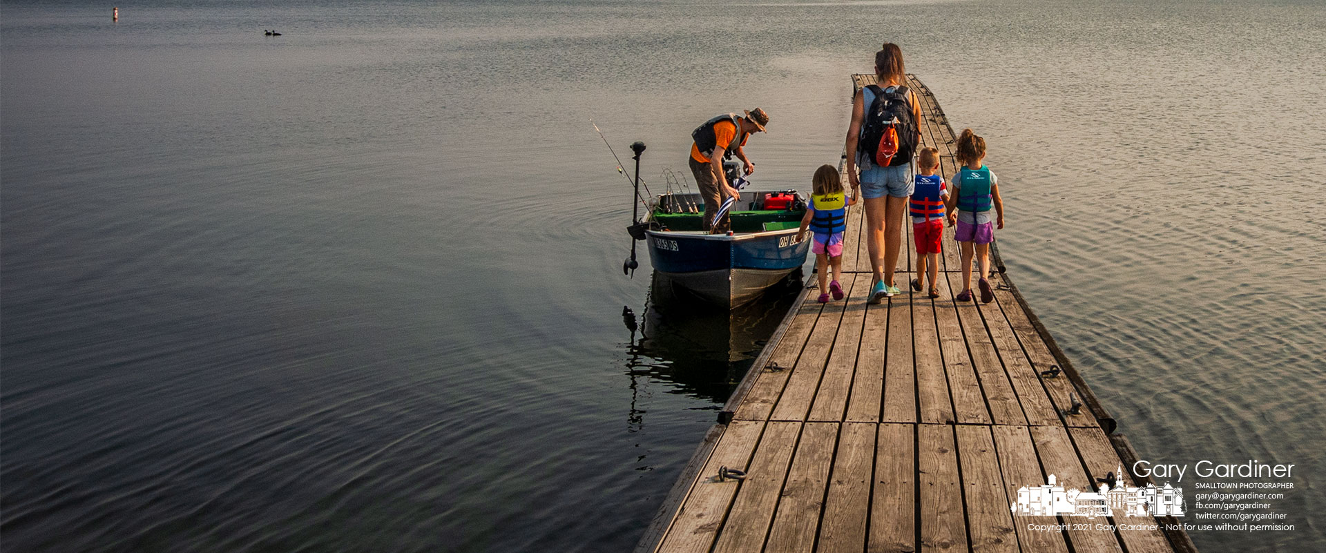 Dad readies the boat as Mom, wearing a backpack filled with snacks, escorts their three children along the Walnut Street boat ramp dock for a day of fishing on Hoover Reservoir. My Final Photo for Sept.13, 2021.