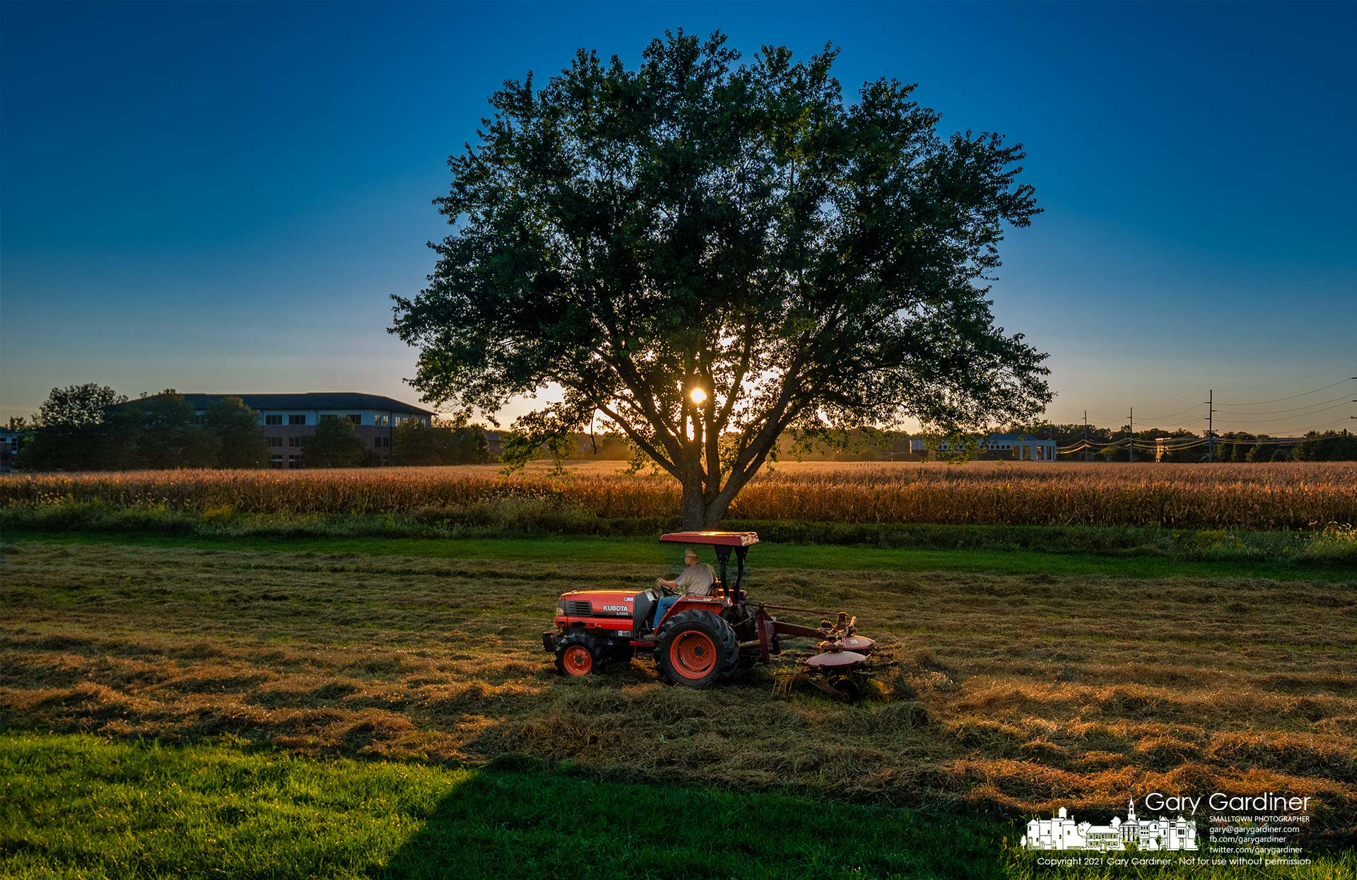 Duane Yarnell rakes hay on the lower section of the small field behind his barn and across the creek from a field of corn. My Final Photo for Sept. 29, 2021.