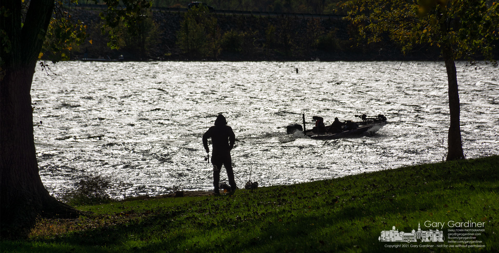 A shorebound fisherman watches as a waterborne compatriot passes by for a better fishing hole at Alum Creek State Park Lake. My Final Photo for Oct. 17, 2021.