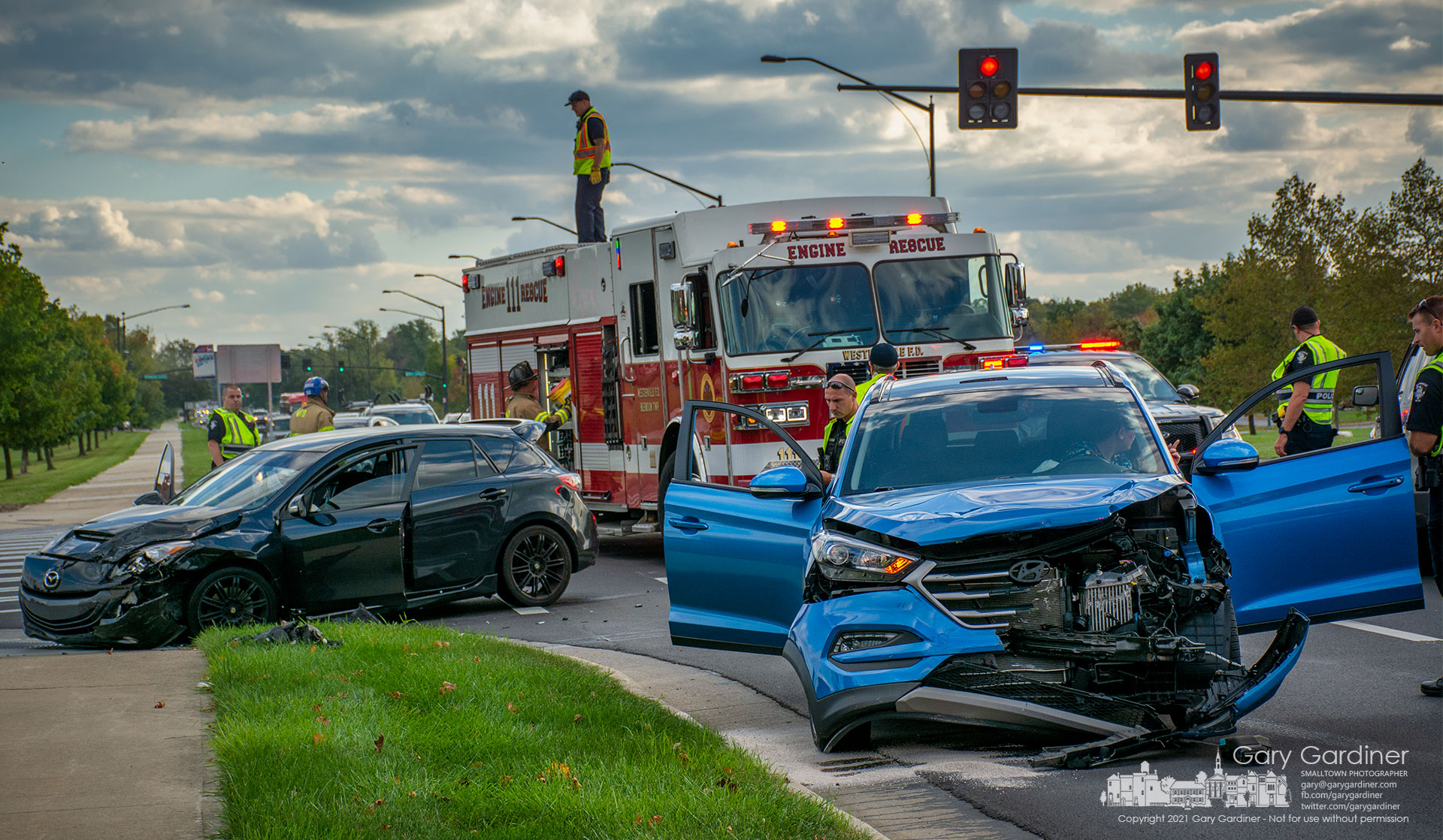 A Westerville firefighter retrieves equipment from the top of a fire truck as police investigate a car crash during rush hour at Cleveland Ave. and County Line Road. My Final Photo for Oct. 12, 2021.