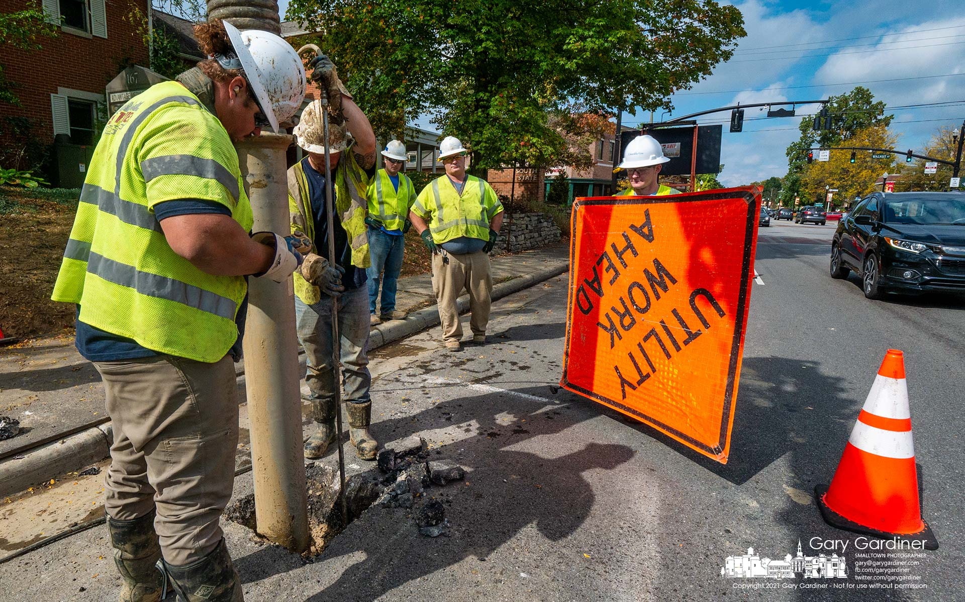 A work crew vacuums debris from a hole cut into State Street near Walnut Street where a pressure cutter cuts away the road to expose a gas line that needs repair. My Final Photo for Oct. 8, 2021.