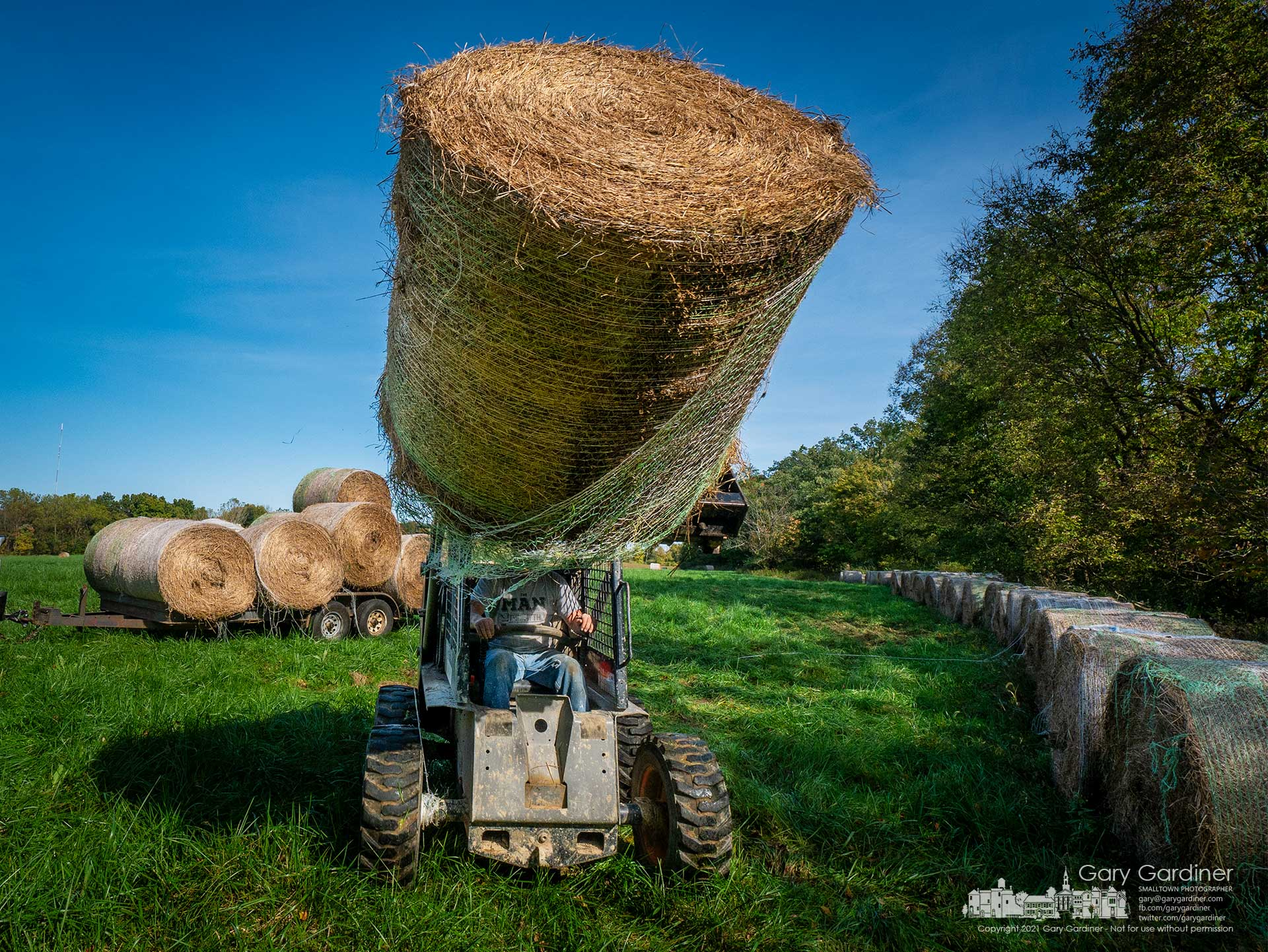 Round hay bales are moved to the edge of the field for temporary storage and to allow the field to grow for what may be another fresh cut before winter. My Final Photo for Oct. 13, 2021.