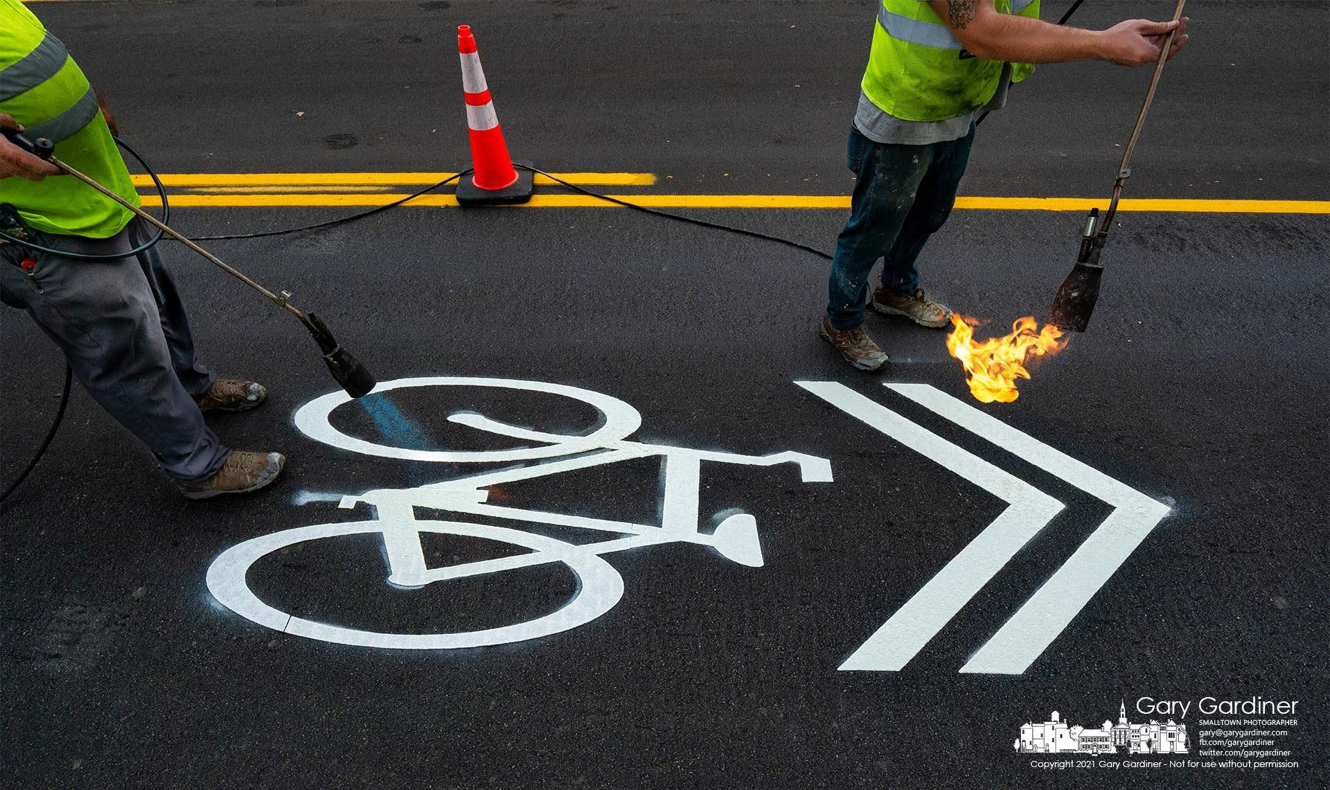 Workers use propane torches to heat and seal plasticized paint strips road markers for motorists on West Main Street marking the roadway is to be shared with bicyclists. My Final Photo for Oct. 4, 2021.